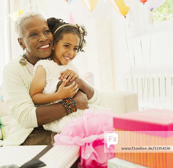 Liebevolle Großmutter und Enkelin beim Umarmen auf der Geburtstagsfeier