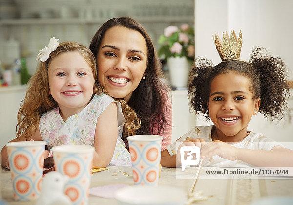 Portrait lächelnde Mutter und Töchter am Geburtstagstisch