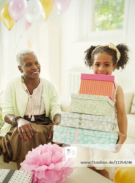 Portrait Mädchen mit einem Stapel Geburtstagsgeschenke