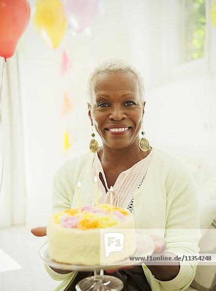 Portrait lächelnde Seniorin mit Geburtstagskuchen