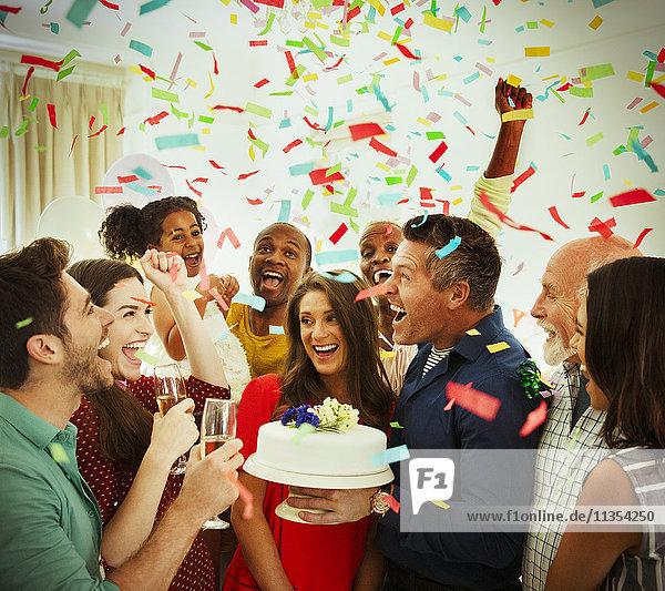 Enthusiastische Familie mit Geburtstagskuchen-Wurf-Konfetti