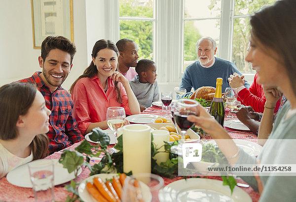 Multi-ethnische Mehrgenerationen-Familie genießt Weihnachtsessen am Tisch