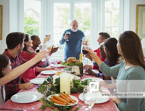 Großvater macht Toast mit Wein am Weihnachtstisch