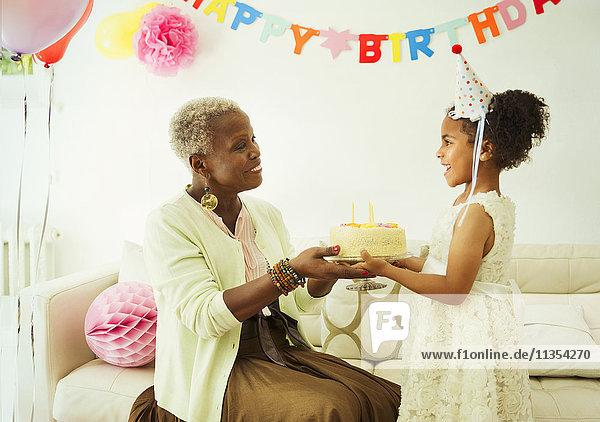 Großmutter und Enkelin mit Kuchen auf der Geburtstagsfeier