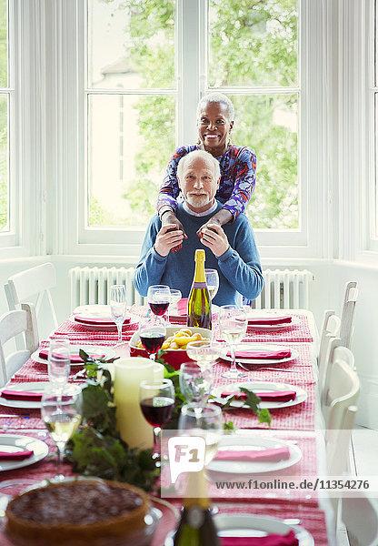 Portrait lächelndes multiethnisches Seniorenpaar am Weihnachtstisch