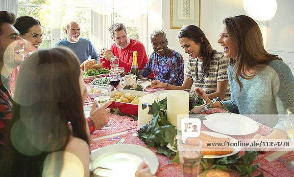 Laughing multi-ethnic family enjoying Christmas dinner at table