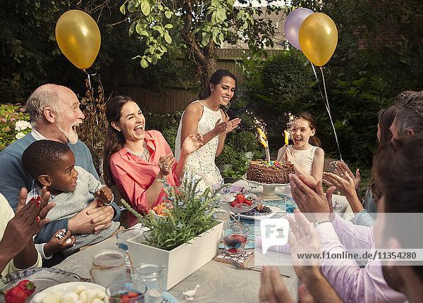 Multi-ethnische Mehrgenerationen-Familienklatschen mit Feuerwerkstorte am Verandatisch