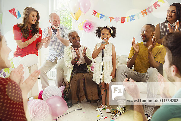 Multi-ethnic family clapping for girl singing karaoke with microphone at birthday party