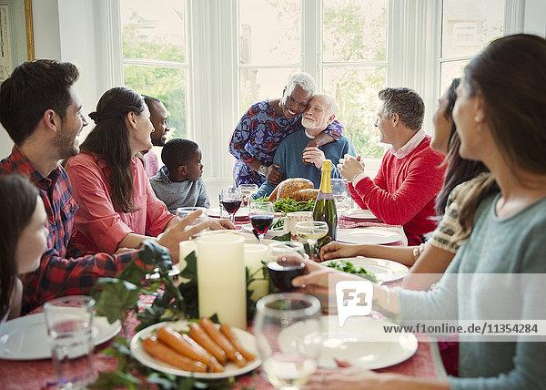 Zärtliches  multiethnisches Seniorenpaar  das sich am Weihnachtstisch der Familie umarmt.