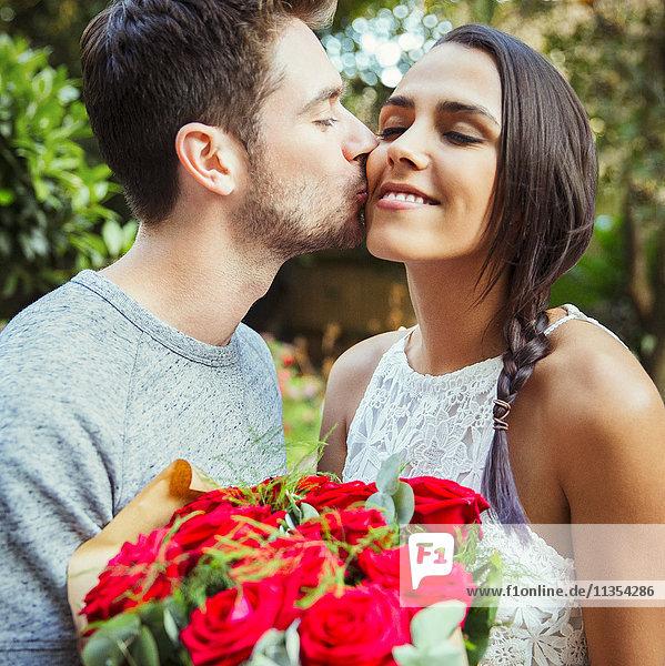 Zärtlicher Mann  der der Freundin einen roten Rosenstrauß schenkt und sie auf die Wange küsst.