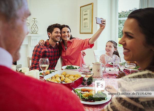 Paar mit Fotohandy  das Selfie am Weihnachtstisch nimmt.
