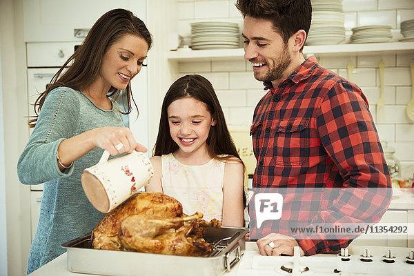 Familie bereitet Weihnachtsessen Truthahn in der Küche vor