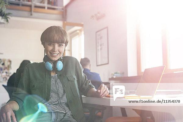 Portrait lächelnde Designerin mit Kopfhörer am Laptop im Büro