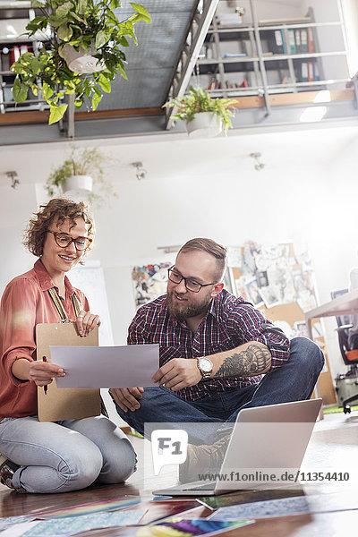 Designprofis diskutieren Proofs am Laptop im Bürogeschoss
