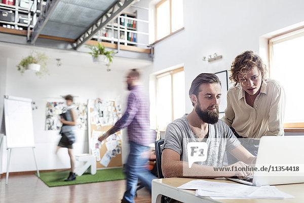 Design-Profis arbeiten am Laptop im Büro