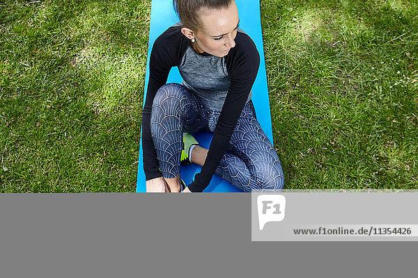 Junge Frau trainiert im Park  bindet die Schnürsenkel der Trainerin auf der Übungsmatte Junge Frau trainiert im Park, bindet die Schnürsenkel der Trainerin auf der Übungsmatte