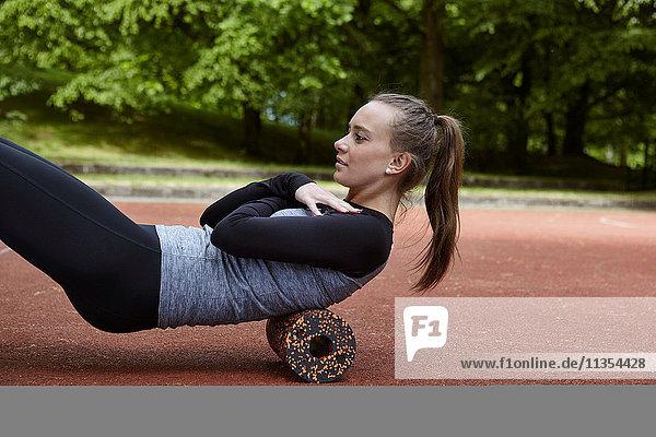 Junge Frau trainiert im Park  macht Rückenrollen Junge Frau trainiert im Park, macht Rückenrollen