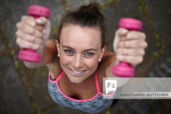 Überkopfportrait einer jungen Frau beim Training  Gewichtheben rosa Hanteln Überkopfportrait einer jungen Frau beim Training, Gewichtheben rosa Hanteln