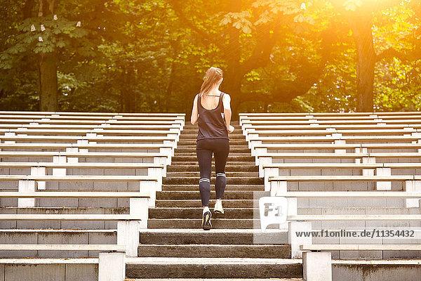 Rückansicht einer jungen Frau beim Training  die die Stadiontreppe hinaufläuft