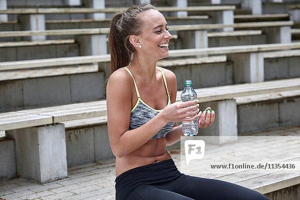 Junge Frau trainiert  macht eine Wasserpause auf der Stadiontreppe Junge Frau trainiert, macht eine Wasserpause auf der Stadiontreppe