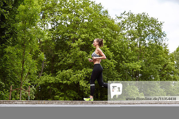 Young woman training  running on top of wall