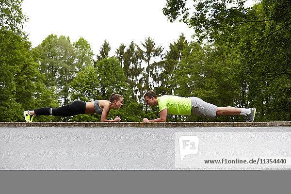 Ein junger Mann und eine junge Frau trainieren und machen Push-Ups gegenüberliegend auf der Mauer Ein junger Mann und eine junge Frau trainieren und machen Push-Ups gegenüberliegend auf der Mauer