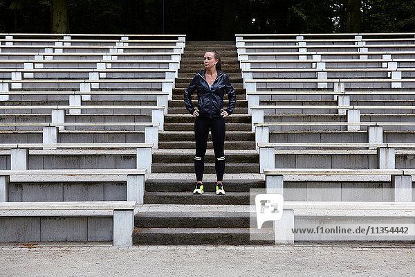 Junge Frau trainiert  bereitet sich auf das Laufen auf der Stadiontreppe vor Junge Frau trainiert, bereitet sich auf das Laufen auf der Stadiontreppe vor