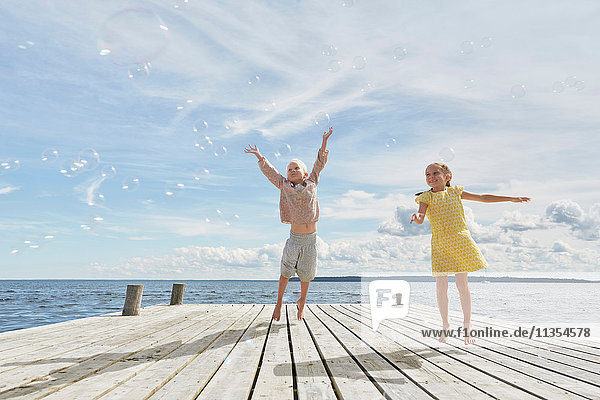Two young friends on wooden pier  jumping to reach bubbles