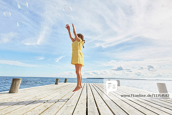 Young girl on wooden pier  jumping to reach bubbles