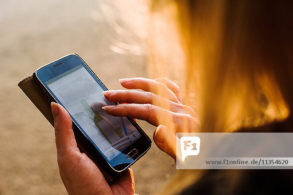 Junge Frau im Freien  mit Smartphone  Nahaufnahme