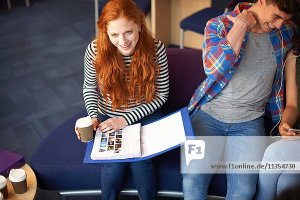 Junge Studentin mit Kaffeelese-Akte zum Mitnehmen im Gemeinschaftsraum
