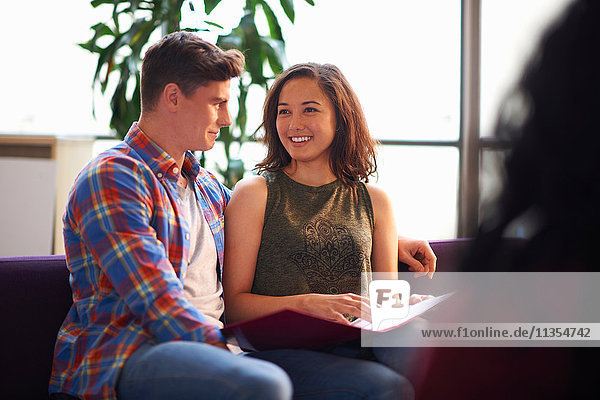 Junger männlicher Student flirtet mit Studentin und liest im Gemeinschaftsraum Akte