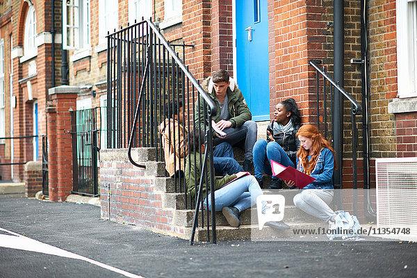 Junge erwachsene College-Studenten lernen auf der Campus-Treppe