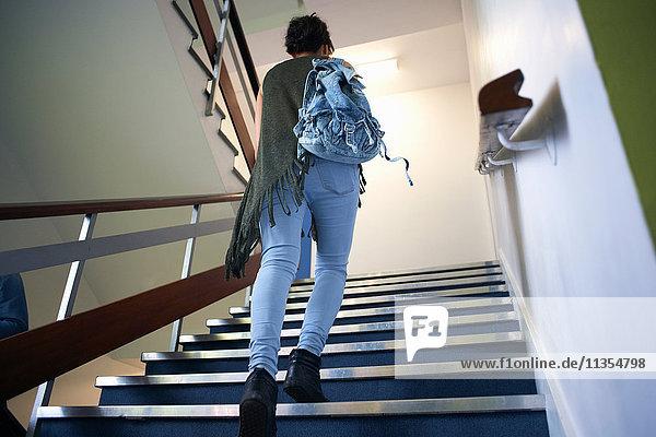 Junge Studentin geht die Treppe hoch