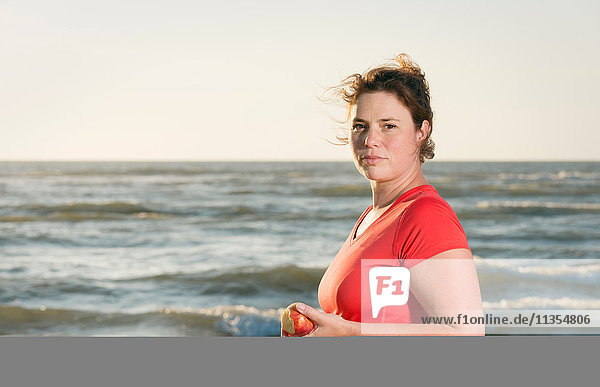 Mature female runner standing on beach at sunset  eating an apple