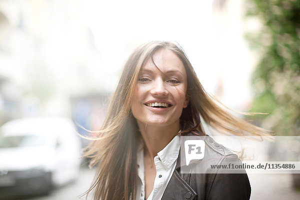 Unbekümmerte Frau mit langen Fliegehaaren auf Stadtstraße