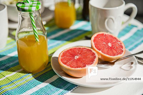 Halbe Grapefruit und eine Flasche Orangensaft Halbe Grapefruit und eine Flasche Orangensaft