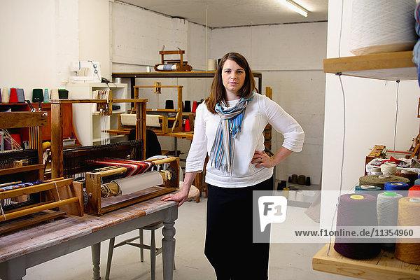 Woman in loom workshop looking at camera