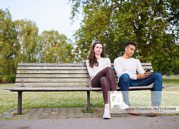 Junges Paar auf Parkbank mit Smartphone