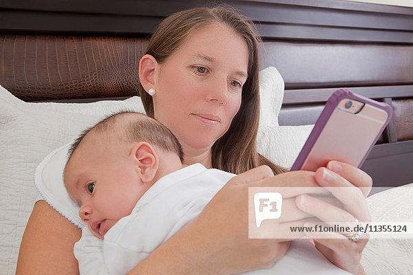 Mutter im Bett hält Baby Junge  der mit Smartphone simst
