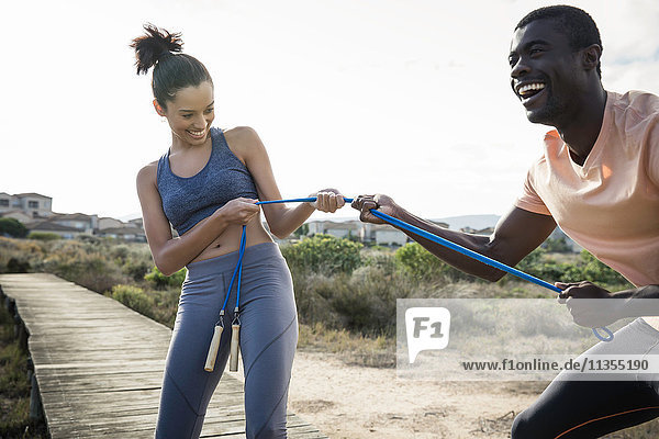 Couple tugging on skipping rope smiling