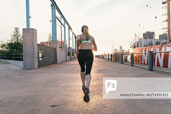Young woman exercising outdoors running along waterfront  rear view  Brooklyn  New York  USA