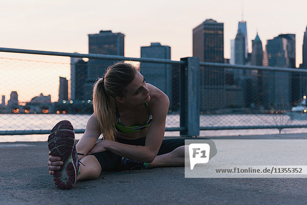 Young woman exercising outdoors  stretching by waterfront  Brooklyn  New York  USA