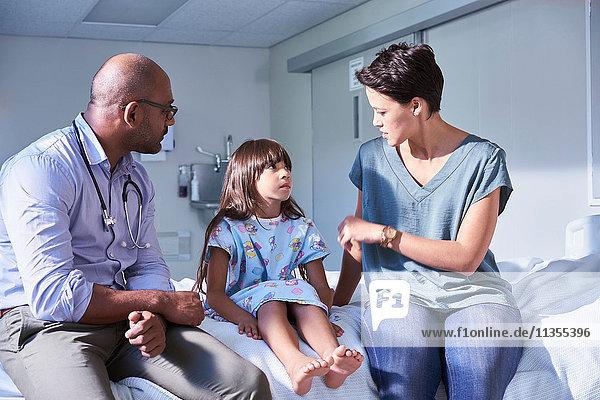 Männlicher Arzt erklärt der Patientin und ihrer Mutter auf der Kinderstation des Krankenhauses