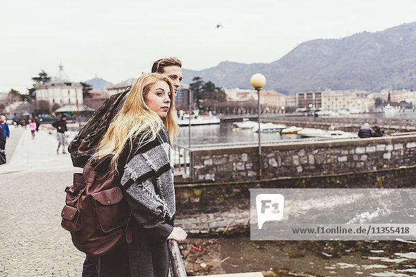 Junges Paar schaut sich am Comer See über die Schulter  Italien