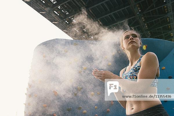 Young woman dusting hands  preparing to use climbing wall  Brooklyn Bridge Park  Brooklyn  New York  USA