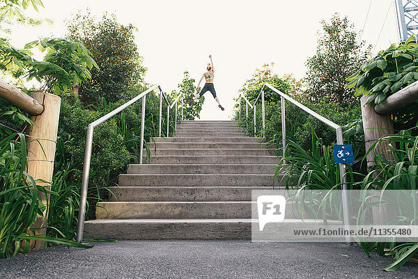 Young woman exercising outdoors  at top of steps  Brooklyn Bridge Park  Brooklyn  New York  USA