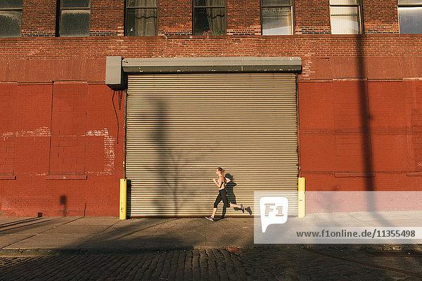 Young woman exercising outdoors  running along street  Brooklyn  New York  USA