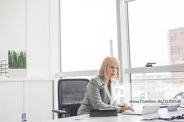 Reife Geschäftsfrau liest Update auf Office-Laptop