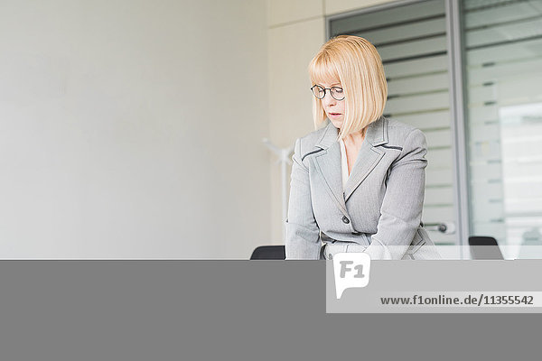 Reife Geschäftsfrau am Schreibtisch mit Touchscreen auf digitalem Tablett
